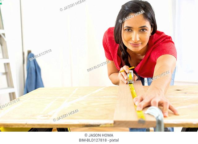 Mixed race woman measuring plank of wood