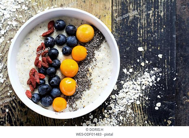 Bowl of porridge with milk, blueberries, chia, physalis and goji berries