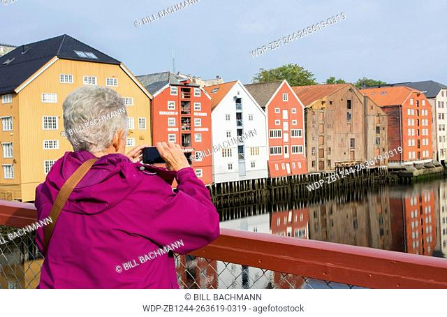 Trondheim Norway cruise Hurtigruten the famous old warehouses with tourist woman taking picture over river with reflections on waters MR-19