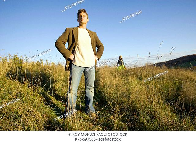 Man standing in field with woman in background