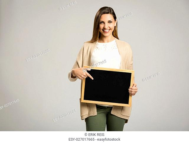 Beautiful and happy woman holding and pointing to a chalkboard