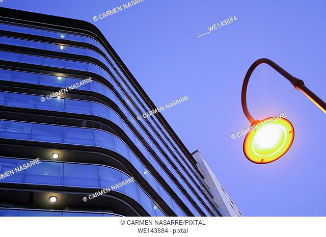 Lamppost and building facade with balconies illuminated, Gijon