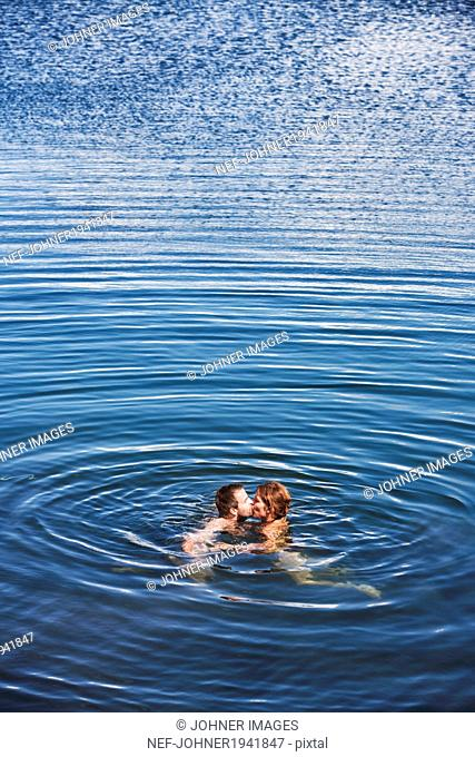 Mid adult couple kissing in sea, Bohuslan, Sweden