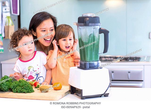 Mid adult woman making smoothie for two toddlers in kitchen