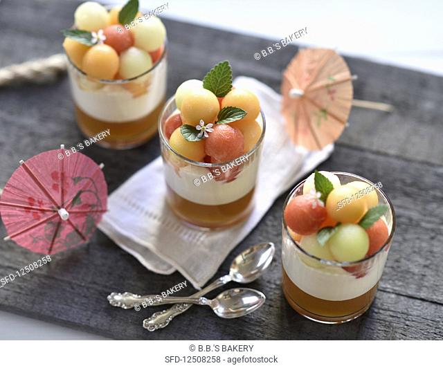 Vegan melon desserts in glasses with melon jelly, whipped sour cream and a trio of different coloured melon balls