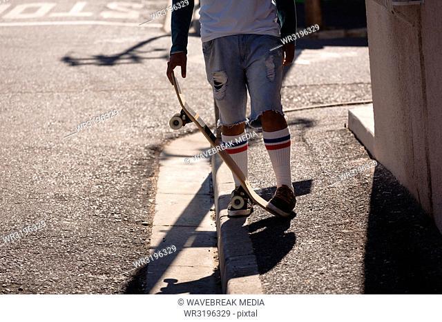 Man standing with skateboard on sidewalk