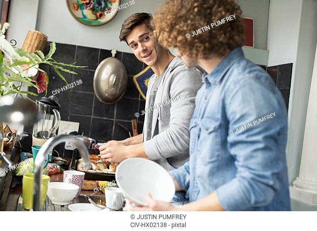 Young men roommates cooking and doing dishes in kitchen