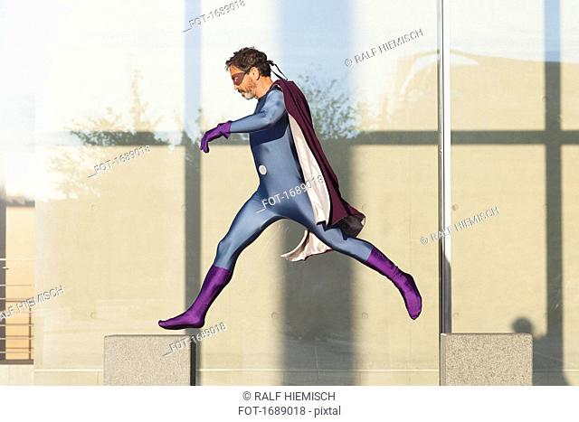 Superhero jumping on concrete against glass wall