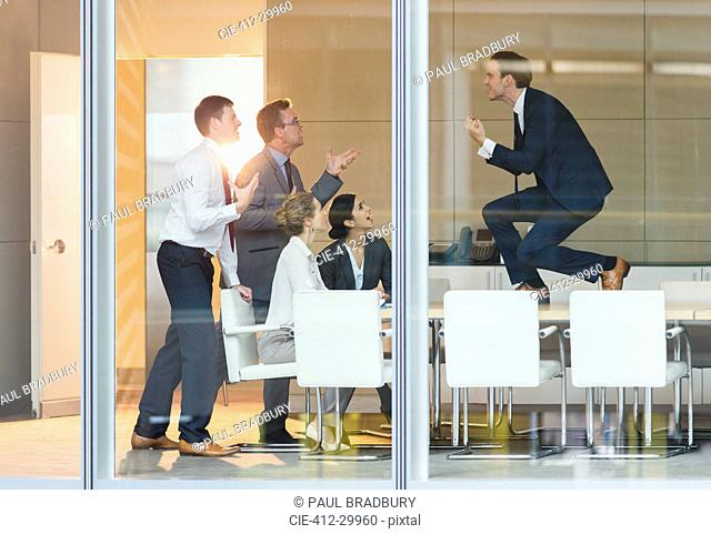 Exuberant businessman gesturing with fists on top of conference table