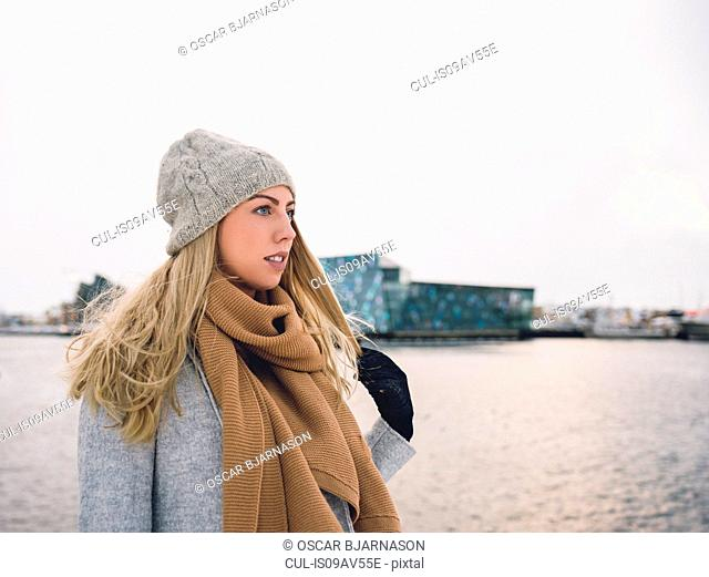 Young woman wearing woollen hat and scarf by water holding hair looking away