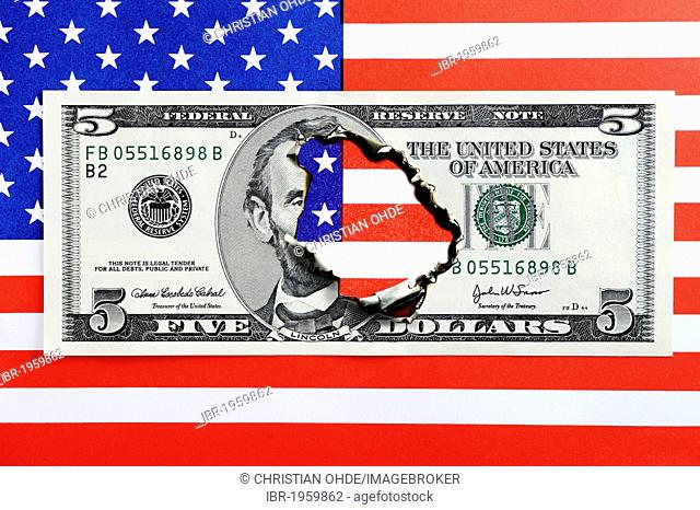 Burnt five-dollar bill on a U.S. flag, symbolic image for the national debt of the USA