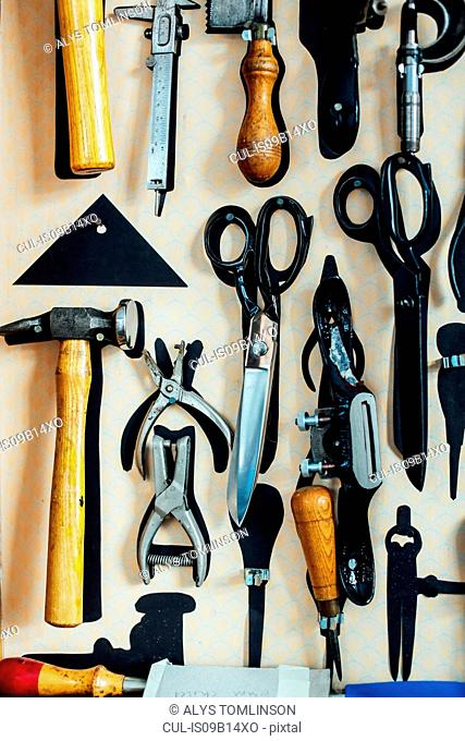 Scissors and tools hanging on wall in arts studio