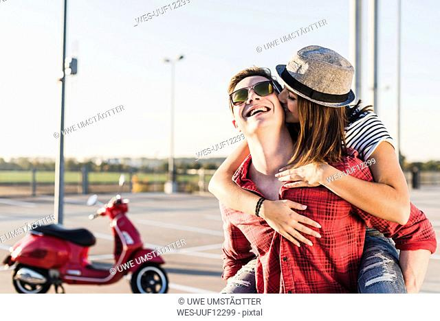 Happy young couple hugging on parking level with motor scooter in background