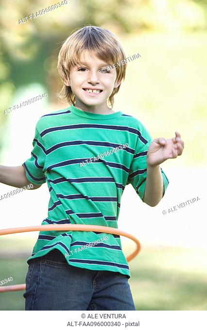 Boy playing with hula hoop in yard