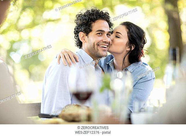 Young woman kissing a happy young man at outdoor table