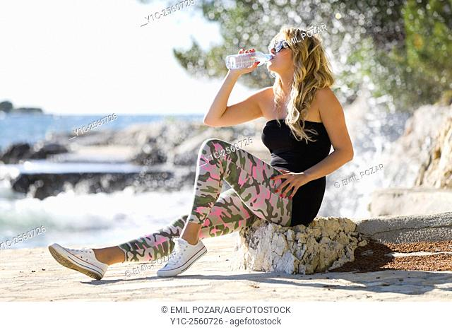 Drinking bottled fresh water young blonde woman
