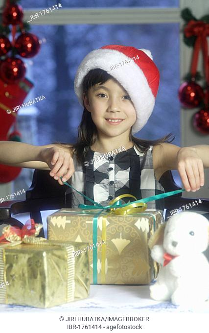 Girl, 10 years, unwrapping Christmas presents