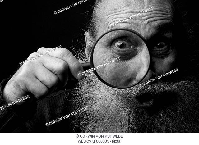 Portrait of an old man looking through magnifying glass