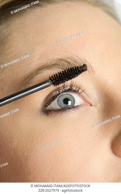 Close up of a young woman applying mascara to eyelashes