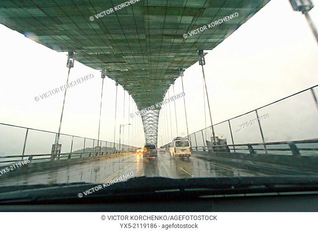 Driving on the Bridge of Americas over Panama Canal during tropical rain