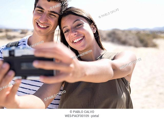 Young couple having fun on the beach, taking smartphone selfies
