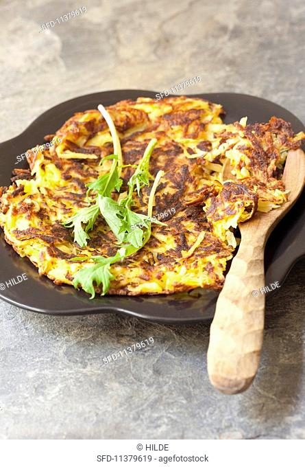 Potato cakes on a plate with a wooden spoon