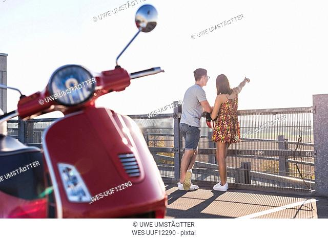 Young couple standing on parking level with motor scooter in foreground