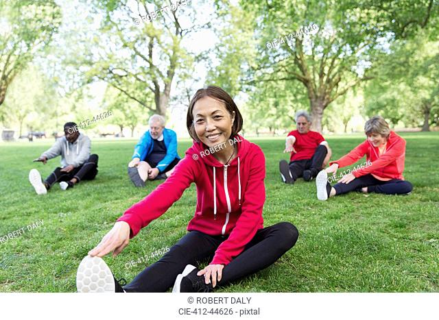 Portrait smiling, confident active senior woman stretching in park