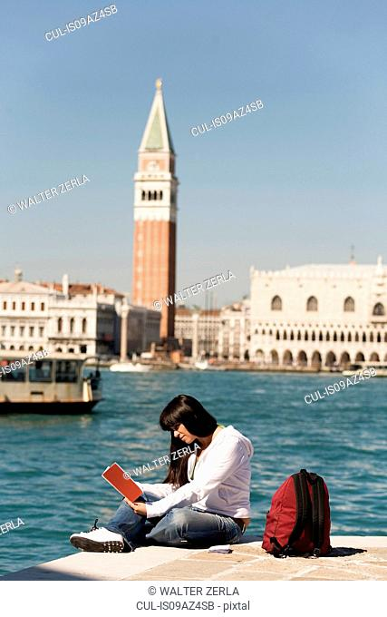 Young woman reading guidebook on waterfront opposite St Marks Square, Venice, Italy