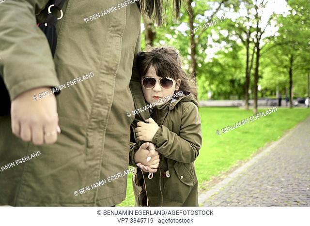 insecure daughter clinging on mother's arm