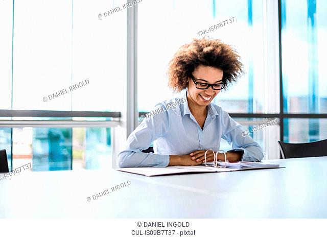 Young businesswoman at desk looking down at paperwork