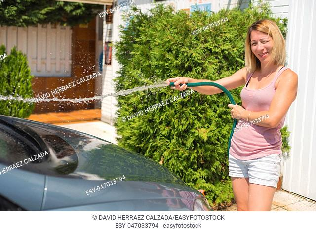 Young woman washing car with hose. Car detailing