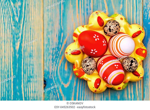 Top view of colorful painted eggs in decorative tray with chicken images on light blue wooden background. Easter background
