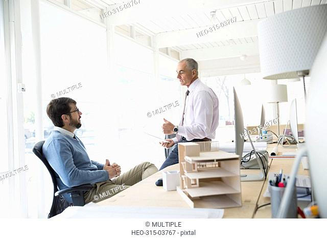 Male architects talking in office