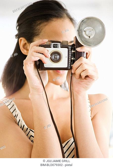 Mixed race woman using old-fashioned camera