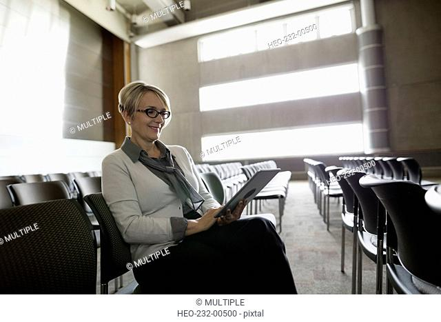 Woman using digital tablet in empty auditorium