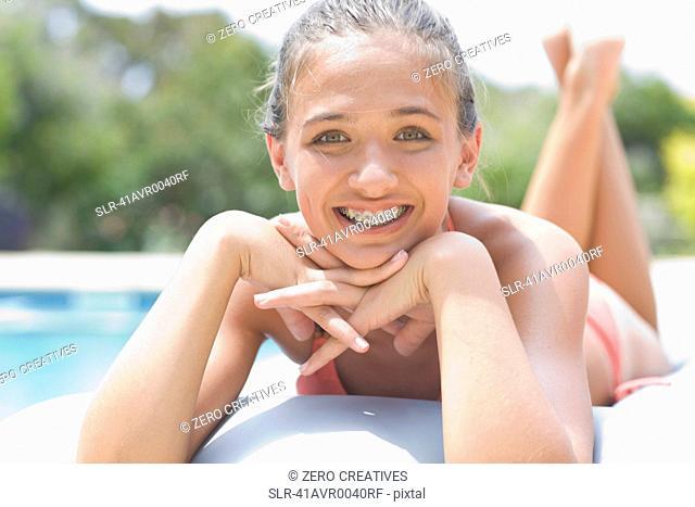 Teenage girl in braces relaxing by pool