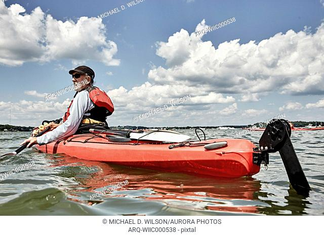 White clouds over man kayaking in red kayak, Portland, Maine, USA