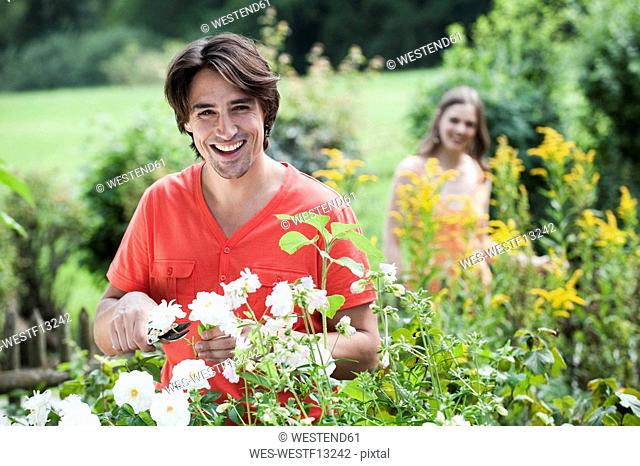 Germany, Bavaria, Man pruning flowers, woman in background, smiling, portrait