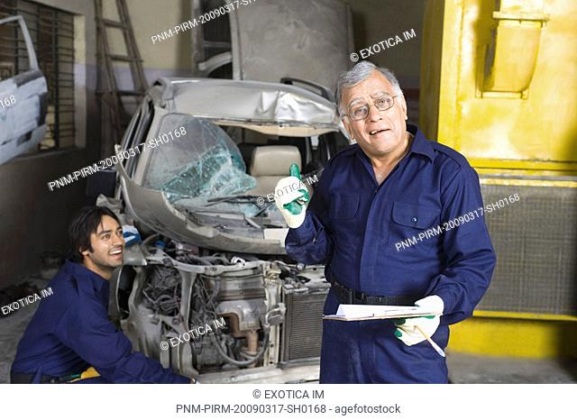 Portrait of an auto mechanic gesturing with an apprentice repairing a car in the background