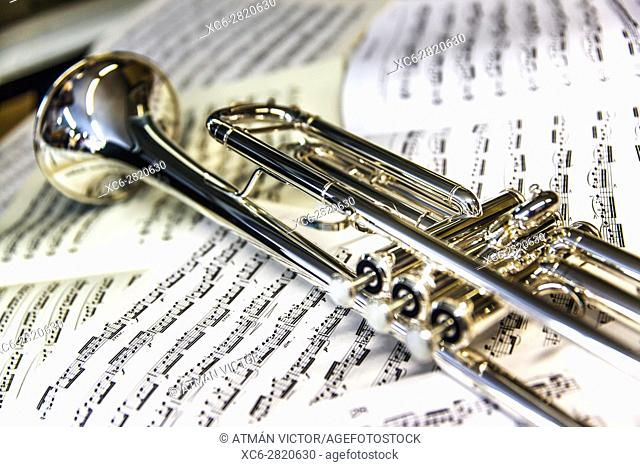 trumpet laying on sheets of music