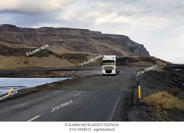 Truck driving over Markarfljot glacial river which flooded during the volcanic eruption in Eyjafjallajokull glacier, South Iceland  Road workers managed to dig...