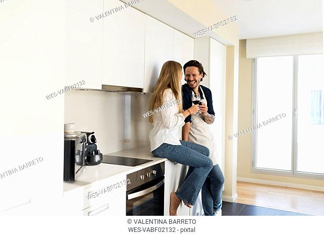 Affectionate couple drinking redwine in the kitchen