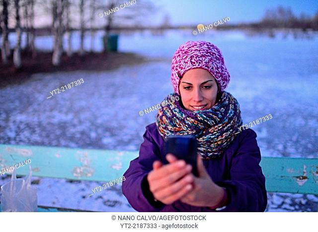 Young woman using mobile telephone in winter environment