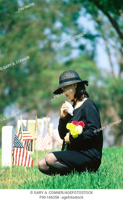Mourning woman at grave site on memorial day