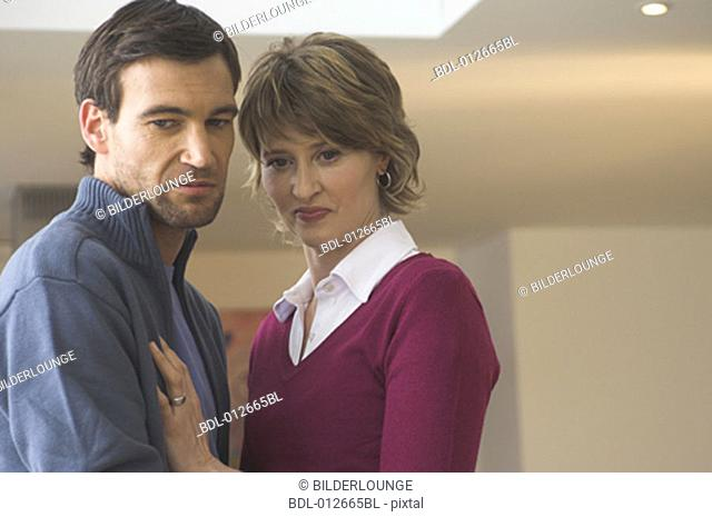portrait of couple with disgusted look on their faces