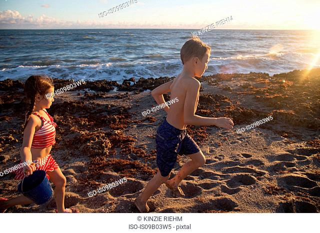 Boy and sister running on beach, Blowing Rocks Preserve, Jupiter Island, Florida, USA