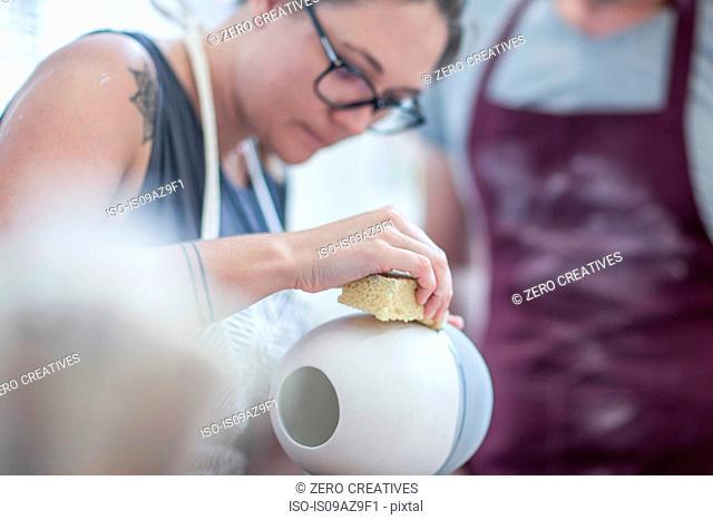 Female potter smoothing surface on vase in workshop