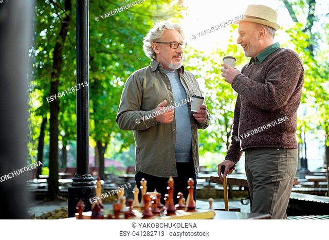Portrait of happy mature men drinking cups of coffee in park and talking. They are standing near chessboard and smiling