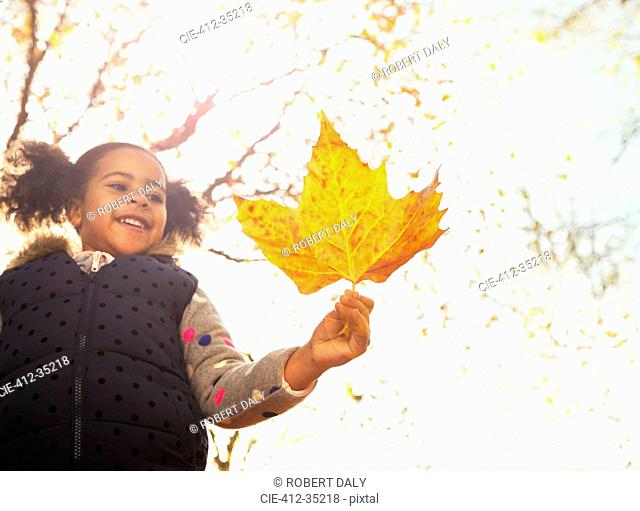 Smiling girl holding orange maple leaf in sunny autumn park